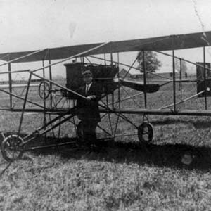 Photograph shows unidentified man posing with early biplane, reportedly first airplane in Chilliwack. Plane was brought to the Chilliwack Fair, ca. 1912 or 1913. [PP501061]