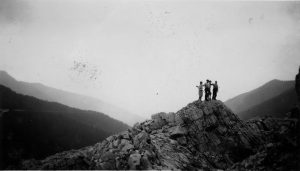 Black and white image of 4 figures standing atop a rocky mountain ride, the background shows the silhouette of mountain peaks in the valley.